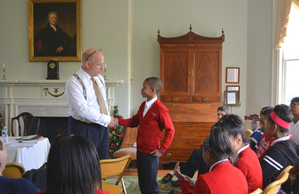 Student participant from Holy Cross School located in Mount Airy shakes hands with Lawyer Scott Griffiths at a program on the constitution hosted by Women for Greater Philadelphia at Laurel Hill Mansion in Fairmount Park on May 1st 2014.