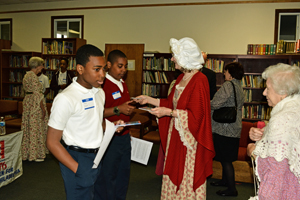 Volunteers from Women for Greater Philadelphia dressed in period costumes hand out a pocket guide to the constitution to the participating students of Holy Cross School.