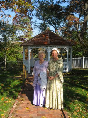 Two women in period costume standing on the path to the gazebo at Laurel Hill Mansion.