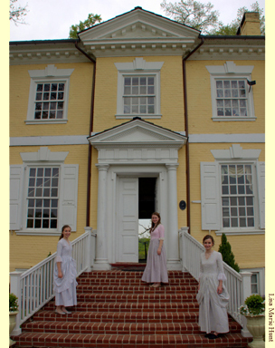Three young women in costume on thesteps leading to the grand entrance of Laurel Hill Mansion